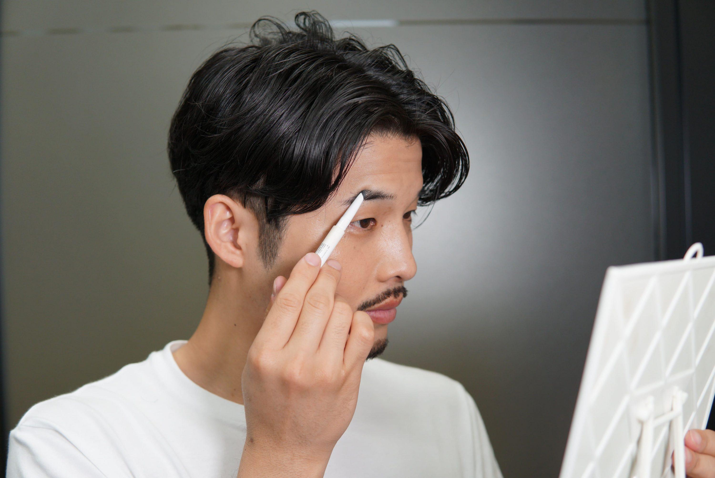 メンズアイブロウペンシルで眉毛を整える男性