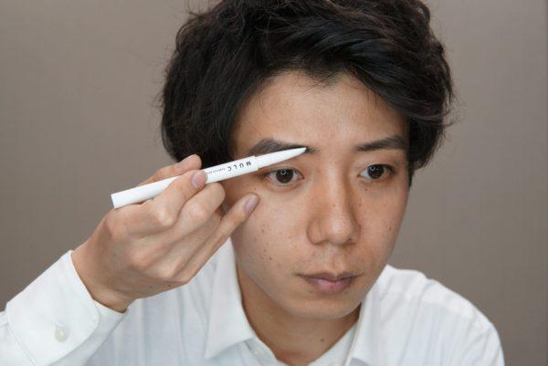 メンズアイブロウペンシルを使って眉頭をかく男性